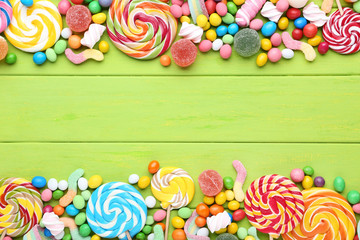 Sweet candies and lollipops on green wooden table