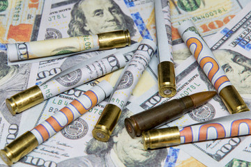rolled banknotes of dollars inside cartridges over hundred dollar bills money and war concept