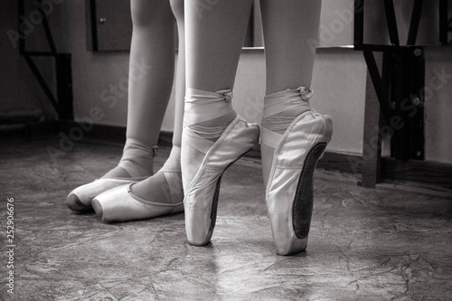 9048fe2986ed5 Close-up of ballerina feet on pointe shoes in the dance hall. Vintage  photography. Close-up of a ballerina in the dance hall. Black and white  photography.