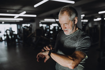 A cheerful senior man in gym measuring time while doing exercise. Copy space.
