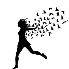 Silhouette of young woman jumping with birds flying from her