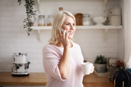 Elegant beautiful mature 45 year old female in stylish sweater holding cup, drinking coffee in kitchen and talking to friend uisng mobile phone, gossiping, having cheerful look, smiling broadly