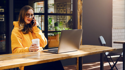 Girl in yellow hoodie sitting in cafe at table, talking on phone while looking to net-book screen. Woman works on laptop