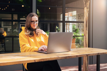 Front view. Girl in yellow hoodie sits in cafe in front of open laptop computer. Woman works on computer, checks email.