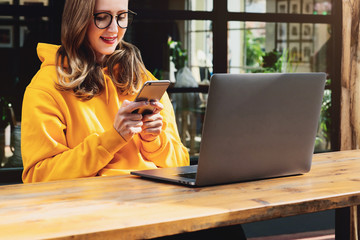 Freelance girl in yellow hoodie sitting in cafe at table front of laptop,using smartphone.Woman typing text message