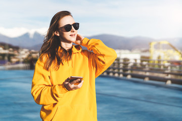 Front view. Girl in yellow hoodie and sunglasses holding smartphone while standing outdoors. In background mountains.