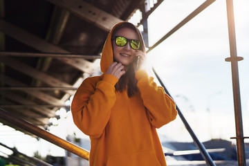 Smiling woman in yellow hoodie, in casual clothes talking on cell phone while standing outside. Girl calls her friend.