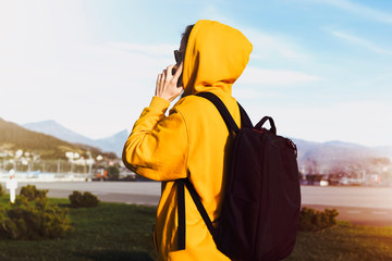 Side view. Girl in yellow hoodie with backpack talking on cell phone. Female traveler calls friends on phone during adventure trip