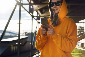 Smiling woman in yellow hoodie with mobile phone standing on street. Girl in hood and sunglasses writes text message on smartphone