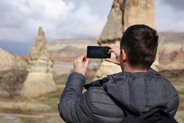 Man tourist taking photo of beautiful Cappadocia mountain landscape. Explore Turkey concept