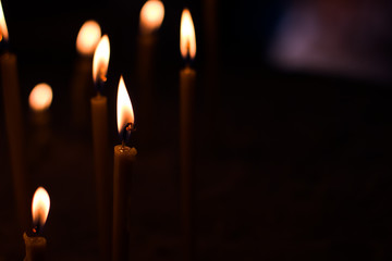 soft focus candles atmospheric photography in deep darkness of Muslim church with background blurred bokeh effect, pattern concept with empty copy space for your text or inscription