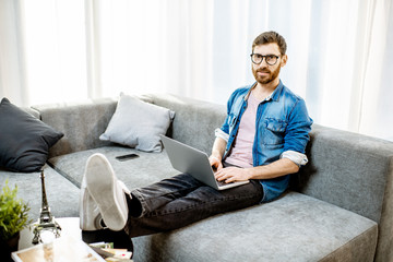 Man working with laptop on the couch at the bright living room of the modern apartment