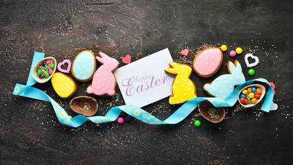 Greeting Easter Background. Easter gingerbread cookies and decorative colored eggs. On a brown background. Top view. free copying space.