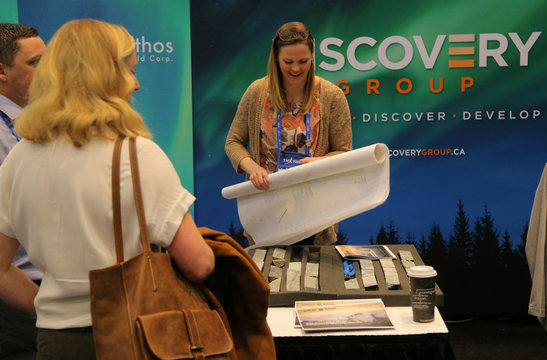 A woman rolls up a map at the Discovery Group booth during the PDAC convention in Toronto