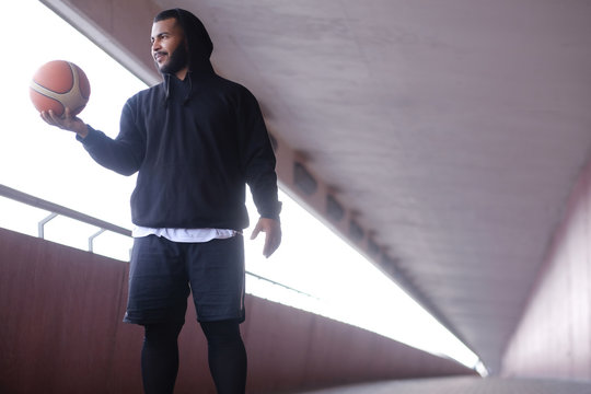 Stylish African-American guy wearing a black hoodie holding a basketball while standing on a bridge sidewalk