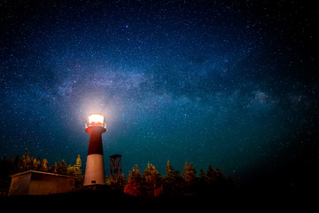A lighthouse at night with a star filled sky above. The light in the top of the lighthouse is illuminated. The Milky Way is visible.