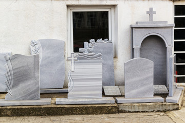 Small private firm produces tombstones and exhibites samples of its products on the street.