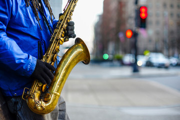 A close-up view of an unidentifiable brass saxophone player on a sidewalk with the street background in bokeh blur.