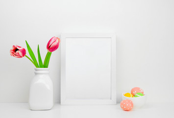 Mock up white frame with Easter Eggs and tulip flowers on a shelf or desk. Easter concept. White color scheme. Portrait frame orientation.