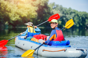 Happy kids kayaking on the river on a sunny day during summer vacation
