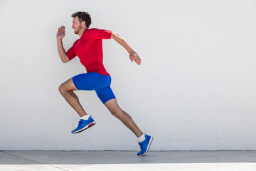 Running man runner training doing outdoor city run sprinting along wall background. Urban healthy active lifestyle. Male athlete doing sprint hiit high intensity interval training.