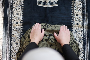 a young Muslim woman praying in the mosque