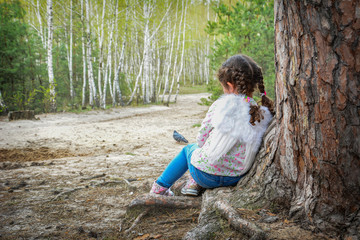 In summer, a small angel is leaning against a tree in the forest.
