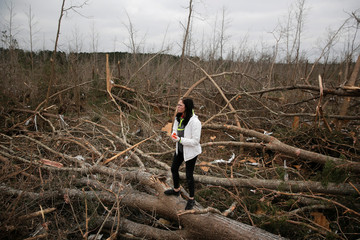 Britney Downs stands on a downed tree trunk after looking through the wreckage of her friend's home after two deadly back-to-back tornadoes, in Beauregard