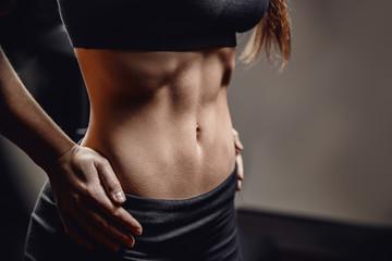 Closeup of drop of sweat on skin abdomen woman after workout. Dark background