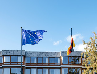 waving European Union blue flag and German flags in front of Federal Constitutional Court building Bundesverfassungsgericht the supreme court for the Federal Republic of Germany