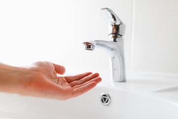 hand under faucet without water