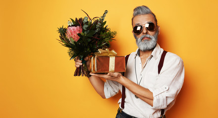 Brutal senior bearded old man in aviator sunglasses with a bunch of flowers and a gift