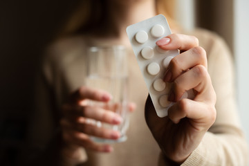 The girl takes the pill, in one hand the medicine in the other glass with water on a dark background. Medicine and treatment