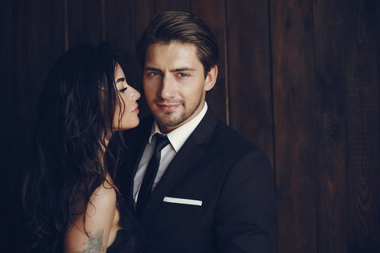 Elegant man in a black suit. Couple at home. Hot woman in a black underwear