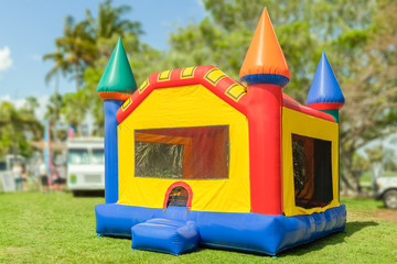 A simple but colorful castle bounce house. The inflated bounce house with pops of color sits at the park on a beautiful sunny day.