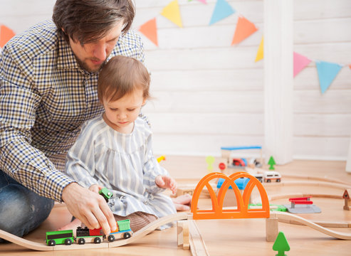 Cute baby girl and her father playing with toy railway road
