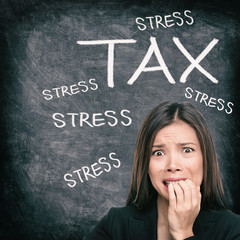 Tax season stress stressed Asian woman biting nails anxious late to file tax paperwork for IRS. Black chalkboard background with text written for income tax returns.