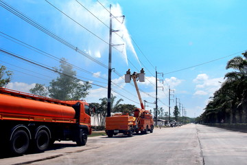 Electricians cleaning wire and Electrical insulator with high pressure water of the power line on power pole with bucket hydraulic lifting platform or electric Picker, Hydaulic platform truck