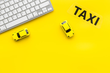 Taxi operator concept. Order taxi online. Sign ner car toy and keyboard on yellow background top view copy space
