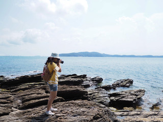 Young girl traveler taking photographs of summer beach.
