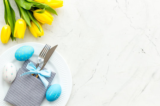 Festive traditional Easter dinner concept. Tableware, painted eggs, tulips flowers on white stone table top view copy space