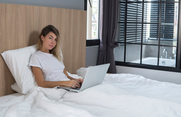 pleasant young woman working on laptop in her bed, girl in bedroom with computer