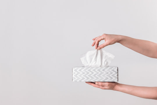 Delicate female hands holding a tissue box