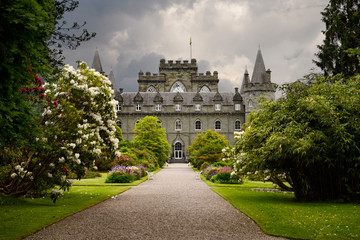 Turretted Inveraray Castle in Gothic Revival style from the flower gardens with dark clouds in the Scottish Highlands Scotland UK
