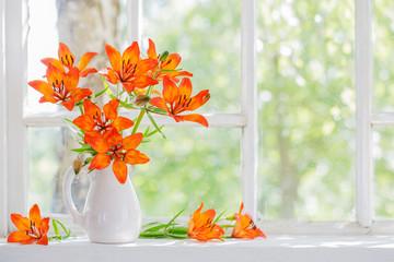 orange lily on windowsill