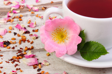 Garden Poster Tea Cup of hot tea with wild rose flower on old rustic wooden background