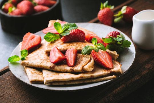Crepes or blini with strawberries on plate. Dark moody food photo. Tasty breakfast or dessert