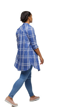 Side view of a young black girl walking in jeans and a checkered shirt.
