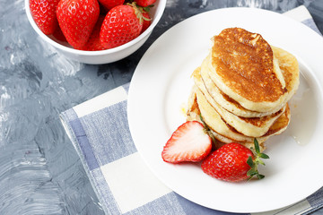 Pancakes on a plate and strawberries on a gray background