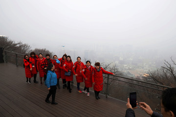 Chinese tourists pose for photographs as a view of the central Seoul is seen in the background shrouded by fine dust during a polluted day in Seoul
